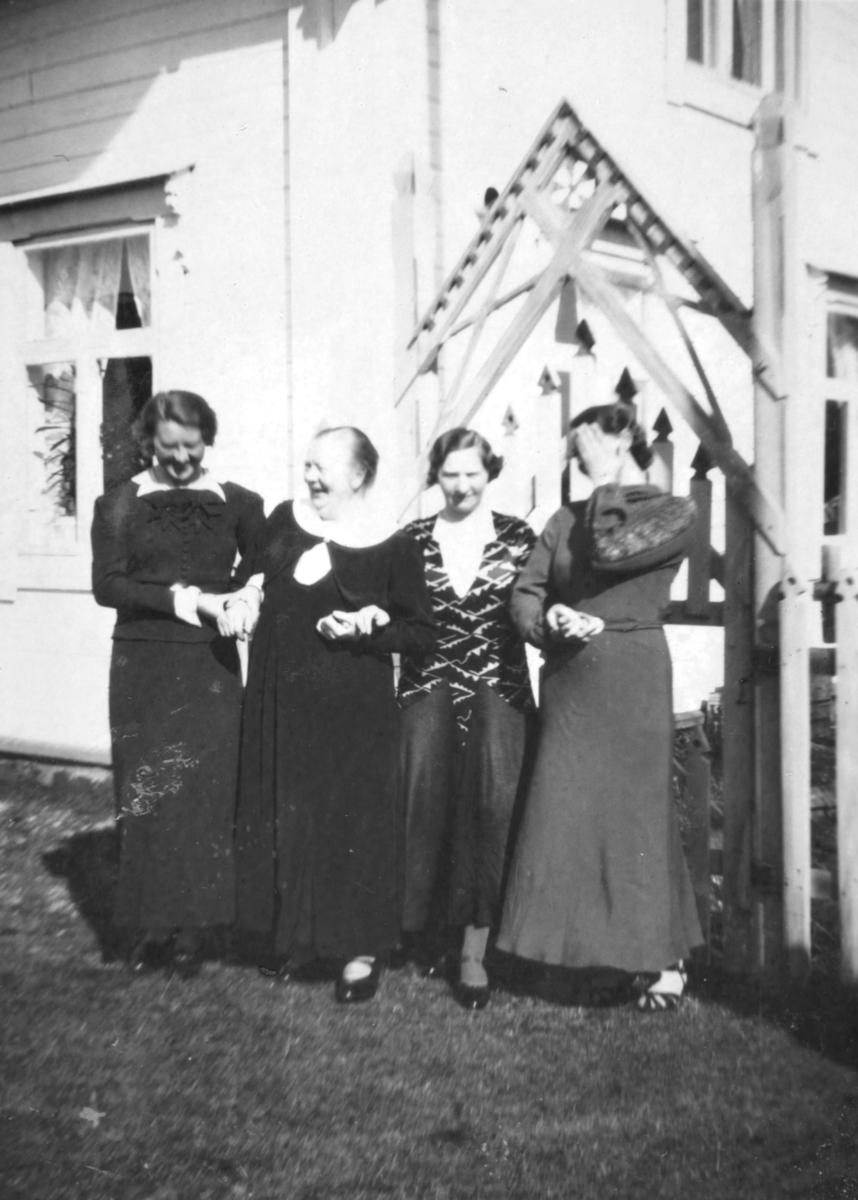 Fire damer som står arm i arm foran en port til et gjerde. Porten en ganske høy og går i en trekant oppe. Damene har pyntet seg og har side kjoler på seg.