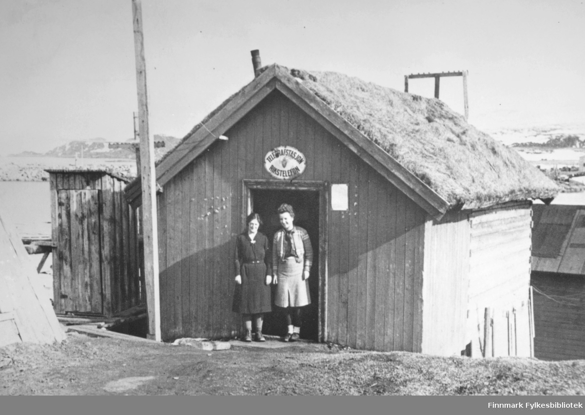 """'Berlevåg herred. Den midlertidige telegraf og telefonstasjon. Betjeningen her vendte tilbake etter et opphold i fjellet 14 dager etter at tyskerene var reist høsten 1944. De fikk utbedret linjen og holdt forbindelsen østover uten å bli oppdaget. De måtte ofte flykte opp i fjellet og gjemme seg midt på natten, når de hørte lyden av en eller annen båt. Mange viktige meldinger ble sendt østover.' -Agnell mai 1946. Ledningsnettet i Finnmark var gjenreist i 1948. Personene på bildet er (iflg. boken """"En søring nordpå Fra gjenreisningstida og brakkeliv i Telegrafverket"""", skrevet av Rolf Køste i 2005) Jorunn Lorentzen og Torgunn Olufsen og de står utenfor det som på folkemunne ble kalt Russebua, som var den midlertidige telegrafstasjonen etter at tyskernes brenning av stasjonen. Jorunn Lorentzen fra Kvitnes var yngst på telegrafen. Forfatter av boken, Rolf Køste, kom til Berlevåg som transmisjonstekniker i 1947."""