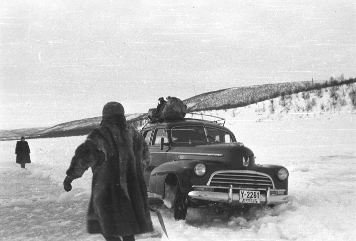 En drosje, Chevrolet 1946 mod,  har kjørt seg fast på isveien over Tanaelva. Noen ukjente personer prøver å hjelpe til med å få den løs.