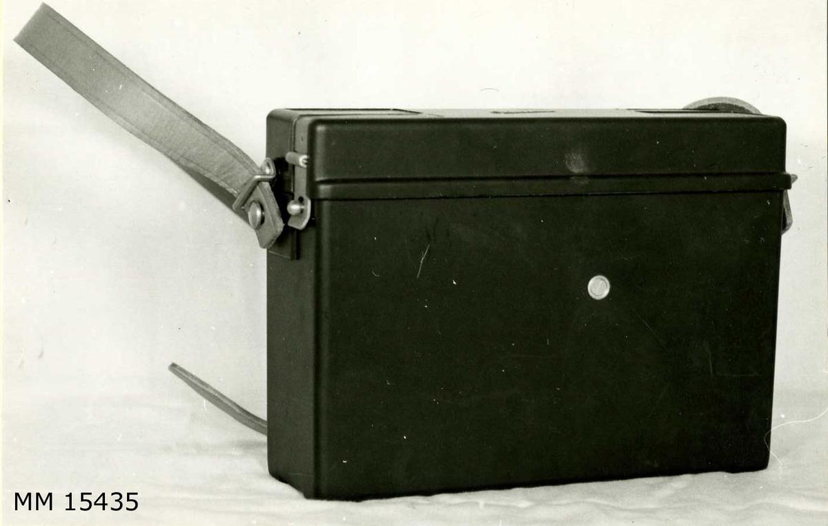 Fälttelefon,  4-kantig grafitgrå plastlåda med lock och axelrem. I lådan förvaras en styck svart handmikrofon i bakelit med tryckknapp i handtaget, en svart mobil fingerskiva samt ett  torrbatteri. Vidare är handmikrofonen och fingerskivan anslutna till en svart enhet i lådan med inkopplingskontakter. Apparaten är tillverkad i Sverige av L M Ericsson.