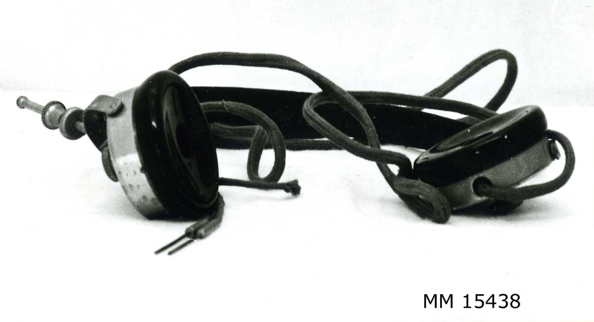 """Huvudtelefon till svensk rundradio. Huvudtelefonen består av två hörlurar sammankopplade med en metallbygel. Hörlurarna har insidor av bakelit och utsidor av metall. Från varje hörtelefon utgår en brunsladd vilken  går samman till en och i vars ände två stiftkontakter sitter. På lurarna är det inristat """"Dr Nesper Phone 2000   """". Lurarna  har svart insida och silverfärgad utsida samt svart bygel."""
