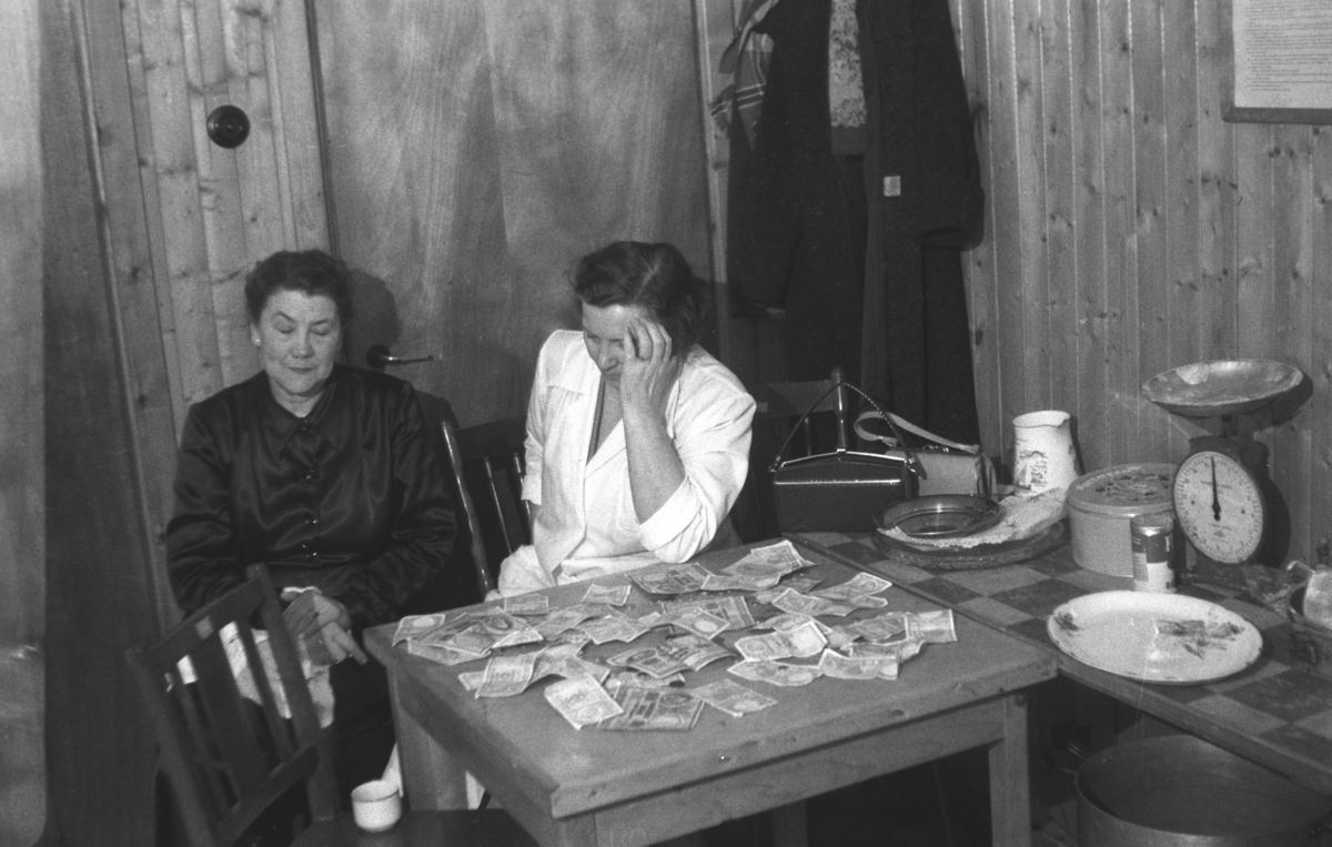Ragnhild Stock og Frida Hauge sitter ved et bord med mange pengesedler liggende oppå.