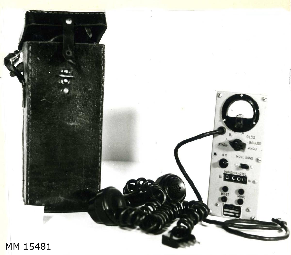 """Kontrollbox för 5 W UK-station m/46 i rektangulär gråmålad låda med mätare överst, samt under denna tre stycken manöverknappar för inställninga av olika funktioner. En stickproppsförsedd handmikrotelefon medföljrer, avsedd att kopplas in i uttag under ovan nämnda manöverknappar. Hela utrustningen med unfantag av handmikrotelefonen förvaras i ett svart läderfodral med bärrem. På fastnitad skylt: """"Kungl Marinförvaltningen, 5 W UK-station M/46, Kontrollbox nr 131"""". Handmikrotelefonen märkt med tre kronor."""