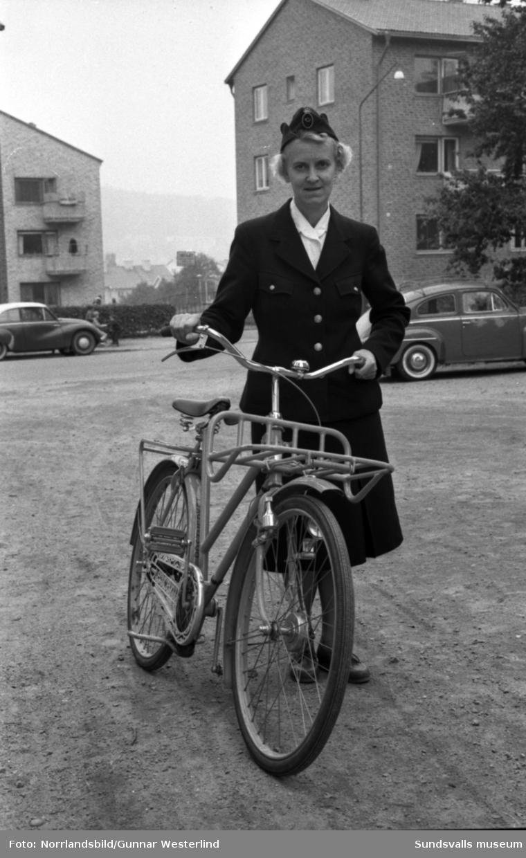 En kvinnlig brevbärare med sin cykel på Sallyhillsvägen.