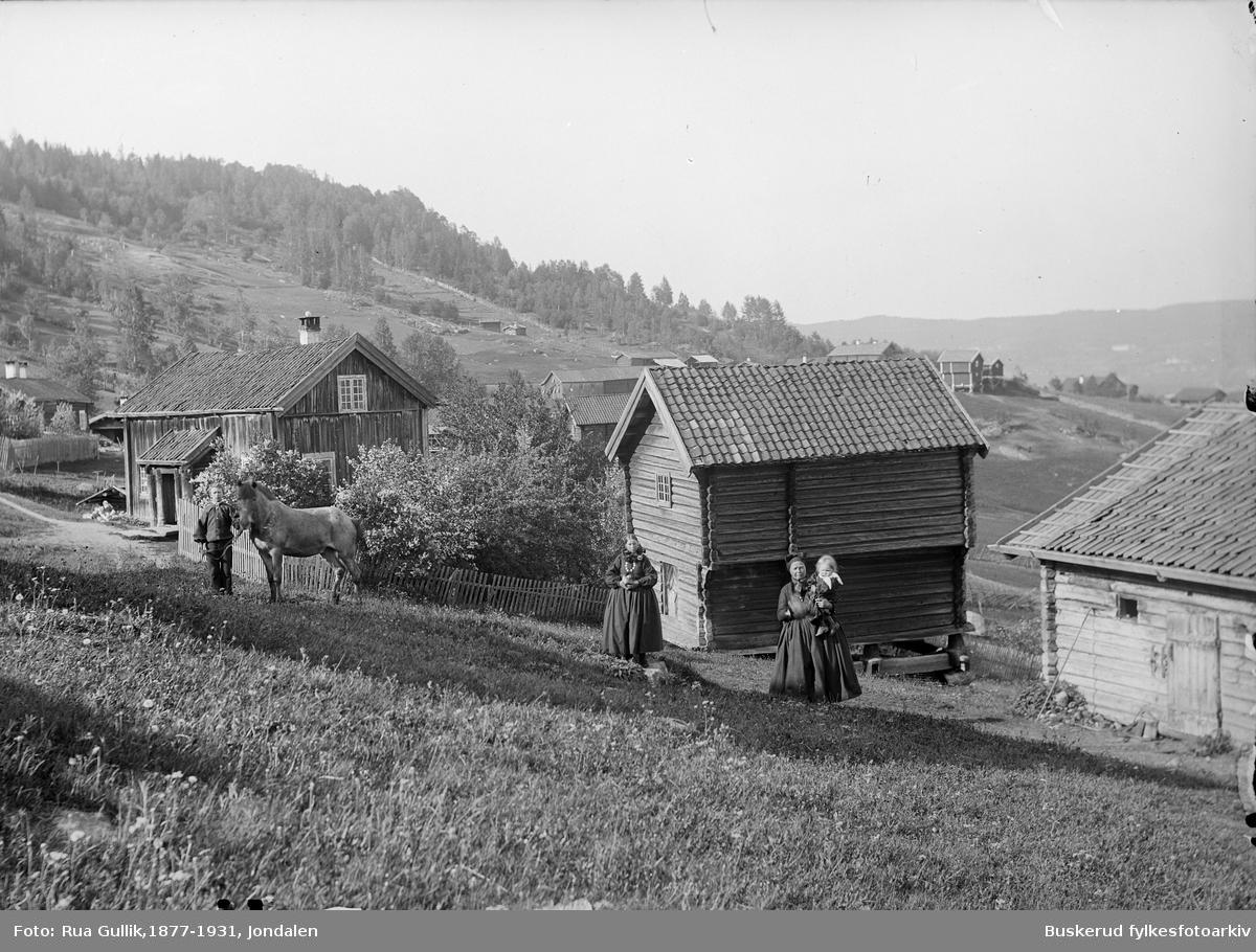 """Jøran Kittilsdatter med dattersønn Kittil på armen. Mor til Kittil er Jøran Sjursdatter . Ole Buin og """"Bronen"""" Flesberg 1899"""