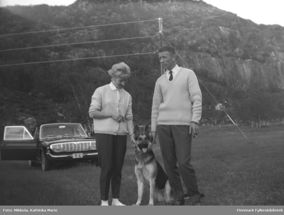 Ekteparet Herlaug og Arvid Digre på Mikkelsnes. Melleom dem en flott schæferhund, og i bakgrunnen står en personbil med skilt Y-4 parkert