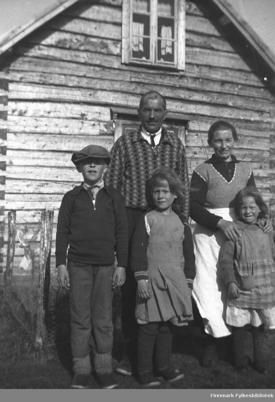 Johan og Beate Mikkola med barna (fra venstre) Åge, Elna og Randi. Bildet er tatt foran et laftet tømmerhus, antakelig hjemmet deres, i Neiden