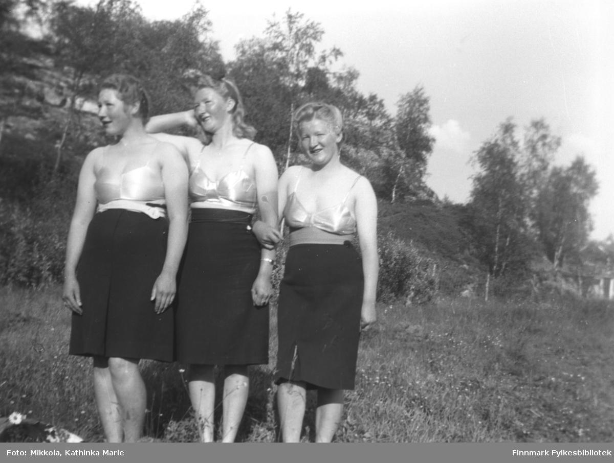Søstrene Kari, Marine og Gudrun Mikkola på Badejordet på Mikkelsnes. Alle tre har badedrakter under skjørtet