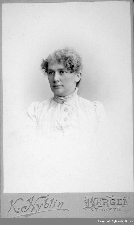 Portrett av en dame i en hvit bluse. Portrettet er tatt hos K. Nyblin atelier i Bergen.