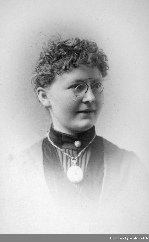 Portrett av en dame. Hun har en lys, tynn jakke med mørk bluse under. En stor medaljong eller et lommeur henger i en kjede rundt halsen og hun har lorgnett på nesen. Portrettet er tatt hos Frederik Klem i Christiania.