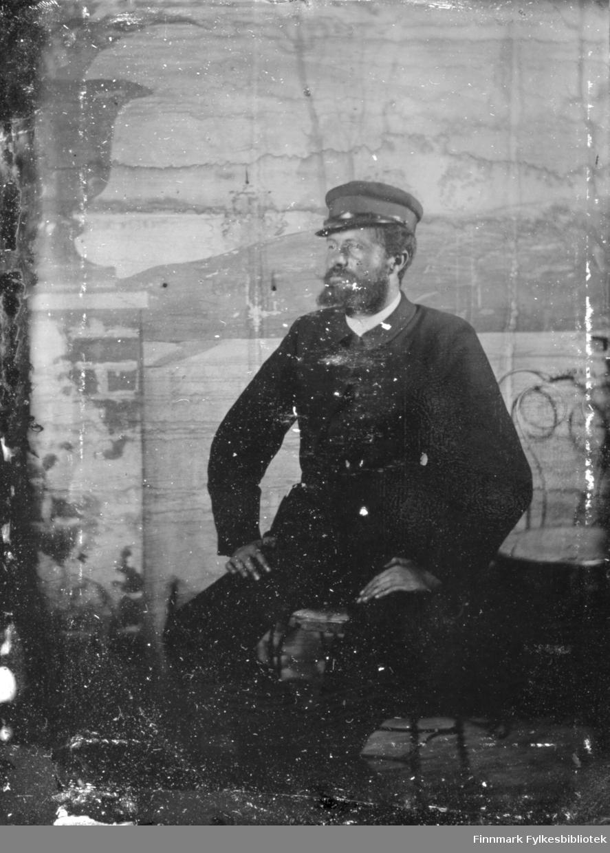 Portrett av en mann i en mørk dress med hvit skjorte under. Han har en hatt på hodet og sitter på en pinnestol. Veggen i bakgrunnen har tapet med et naturmotiv på.