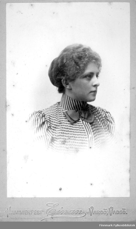 Portrett av en kvinne iført en bluse med striper og mønster. Blusen har en høy krage og en mørk, ensfarget sløyfe er festet i kragen foran.