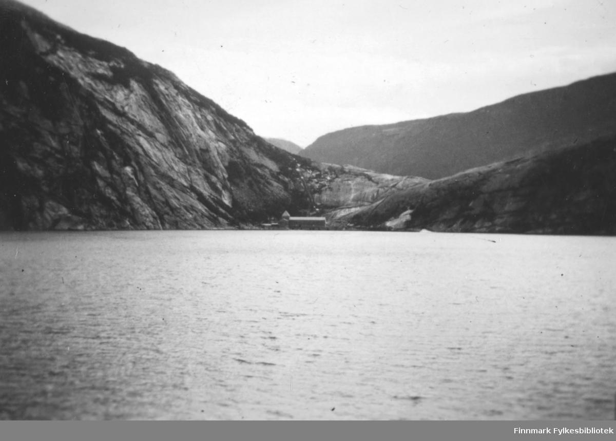 En bukt/liten fjord med høye fjell rundt. De går ned og møtes i midten av fjorden. Et bygg ligger i sjøkanten innerst i fjorden. Krusninger på sjøen vitner om lite vind. Lettskyet og ingen snøflekker i fjellene.