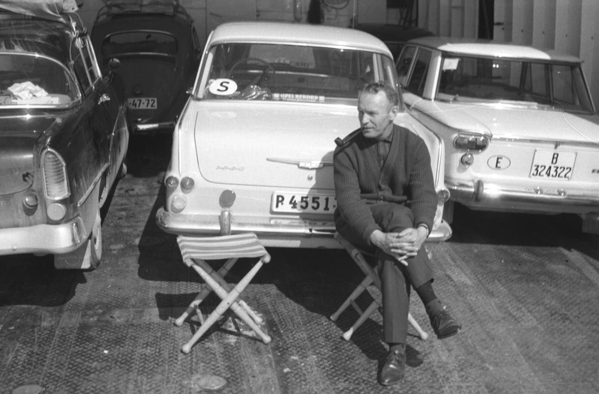 En ukjent mann sitter på en klappstol, muligens på et fergedekk. Bilen som står til venstre er en Opel Rekord P 1958-60 mod. Rett bak mannen står en lys Opel Rekord P2 1961-1962 mod. og til høyre står en Fiat 1300/1500, kan også være en Seat. I bakgrunnen kan hekken på en VW Boble ses.