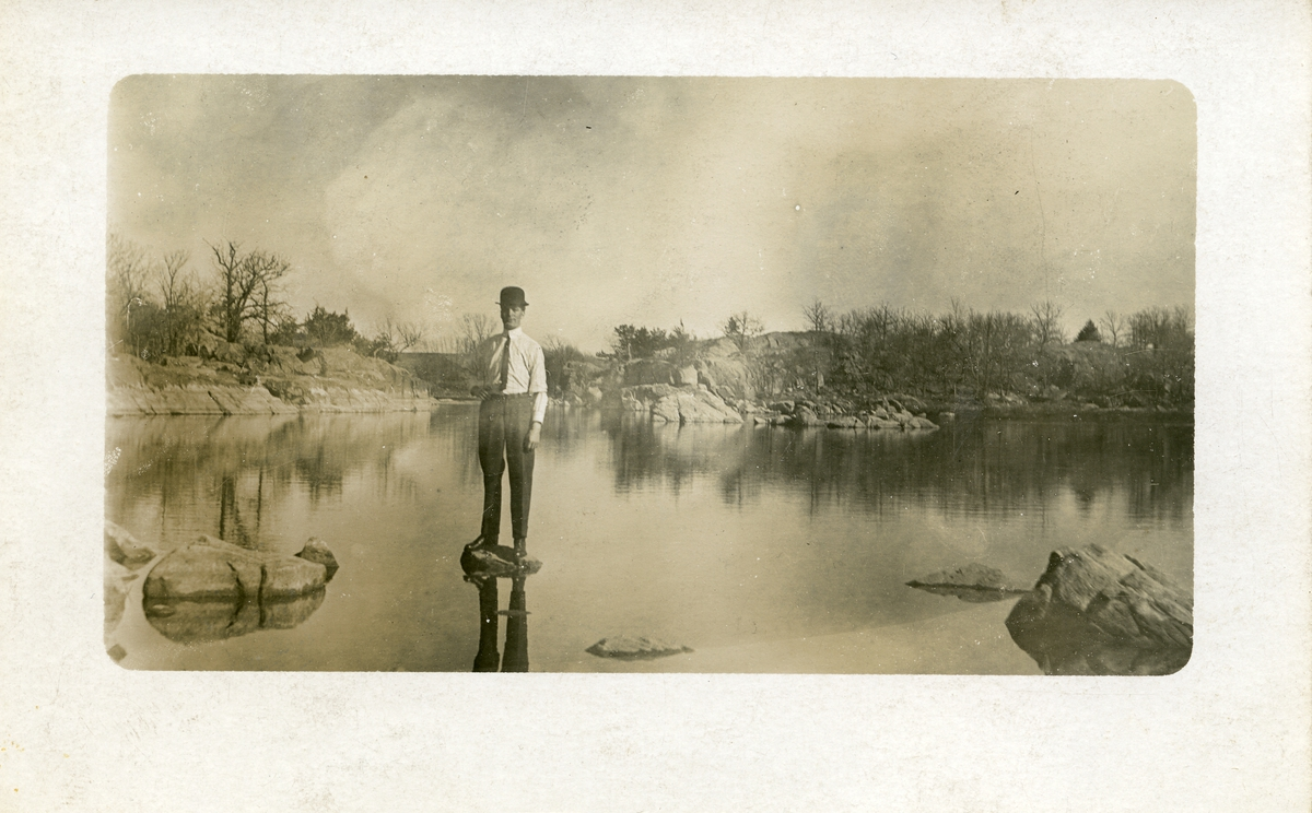 Mann avbildet på stein i vannkanten. Mannen er iført skjorte og slips  og med hatt. Dette er et prospektkort.