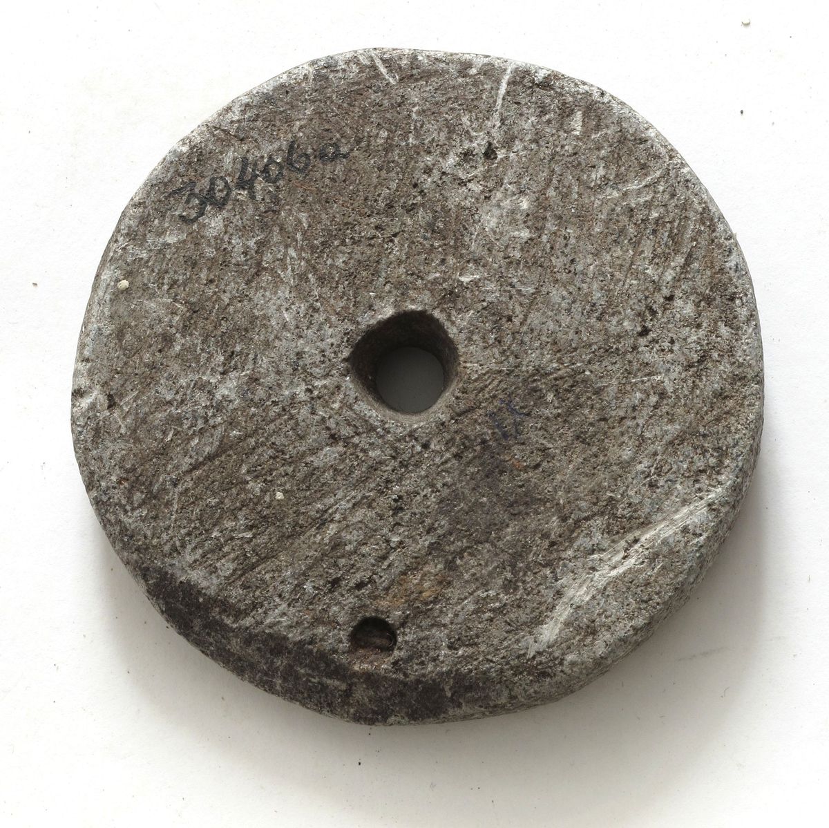 """Skiveformet hjul av lys grå kleber, """"Kjerringrokk"""", til drillbor. Nær kanten er et lite gjennomgående hull med isittende jern. På den ene side løper en grunn fure langs kanten, mellom denne og det forannevnte hull."""