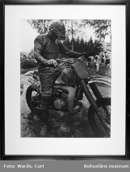 Signifikativt för VM-crossen i Stenungsund. Segraren Håkan Carlqvist, med 30 kilo lera på sig. Maj 1983.