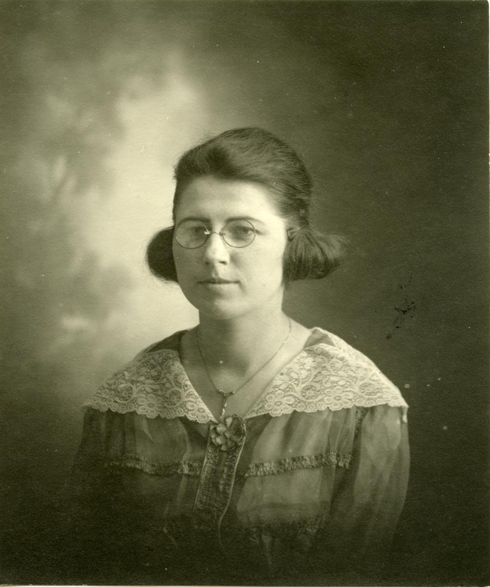 Portrett av kvinne foran lerret. Kvinnen er iført kjole med stor krage og briller.
