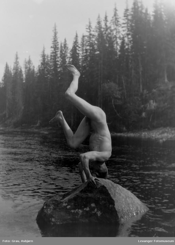 Mann står på hodet på en stein i elva