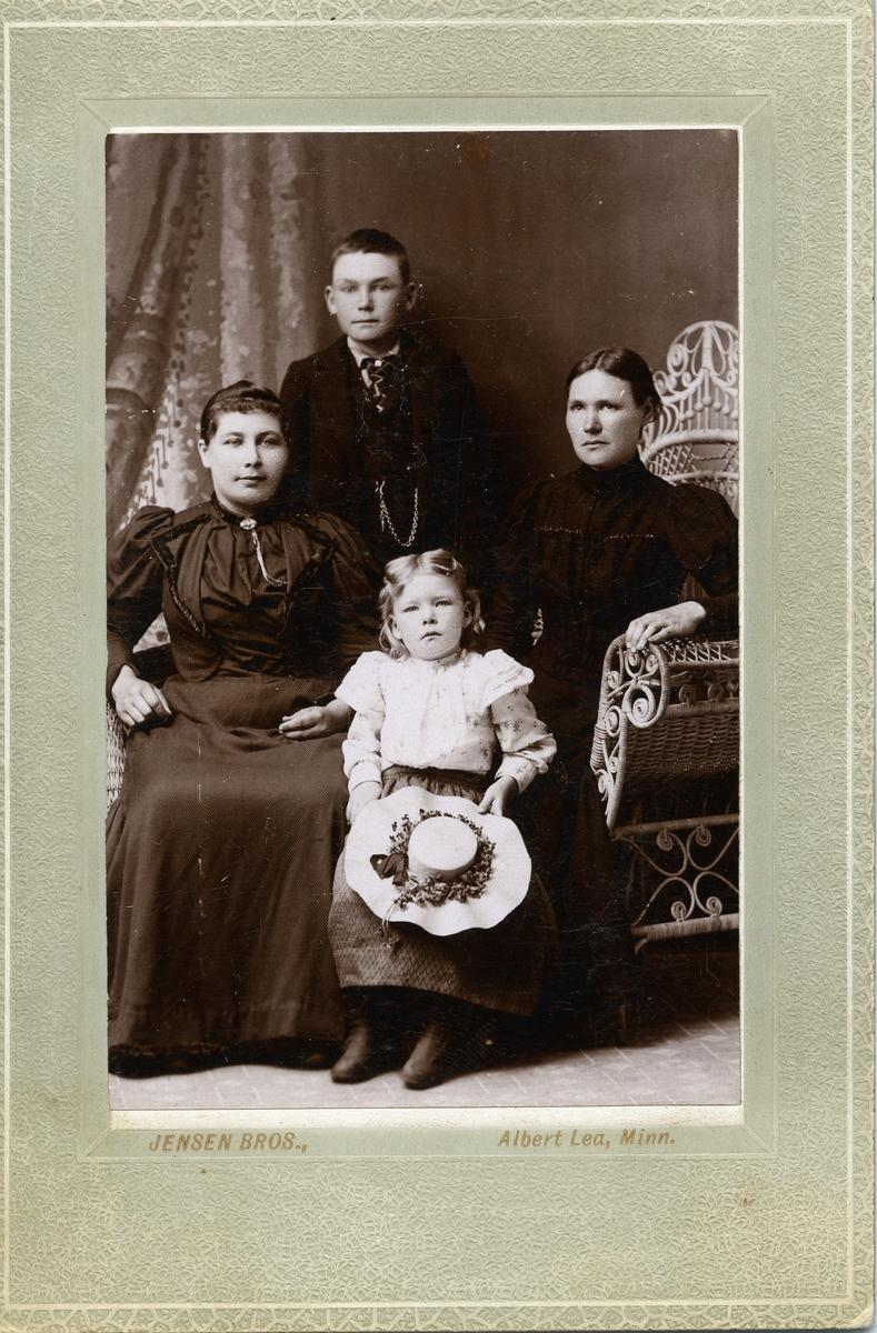 Portrett av to kvinner og to barn (gutt og jente). Kvinnene er kledd i mørke kjoler, jenta har lys, blomstrete bluse og stråhatt. Gutten har dress og lommeur.