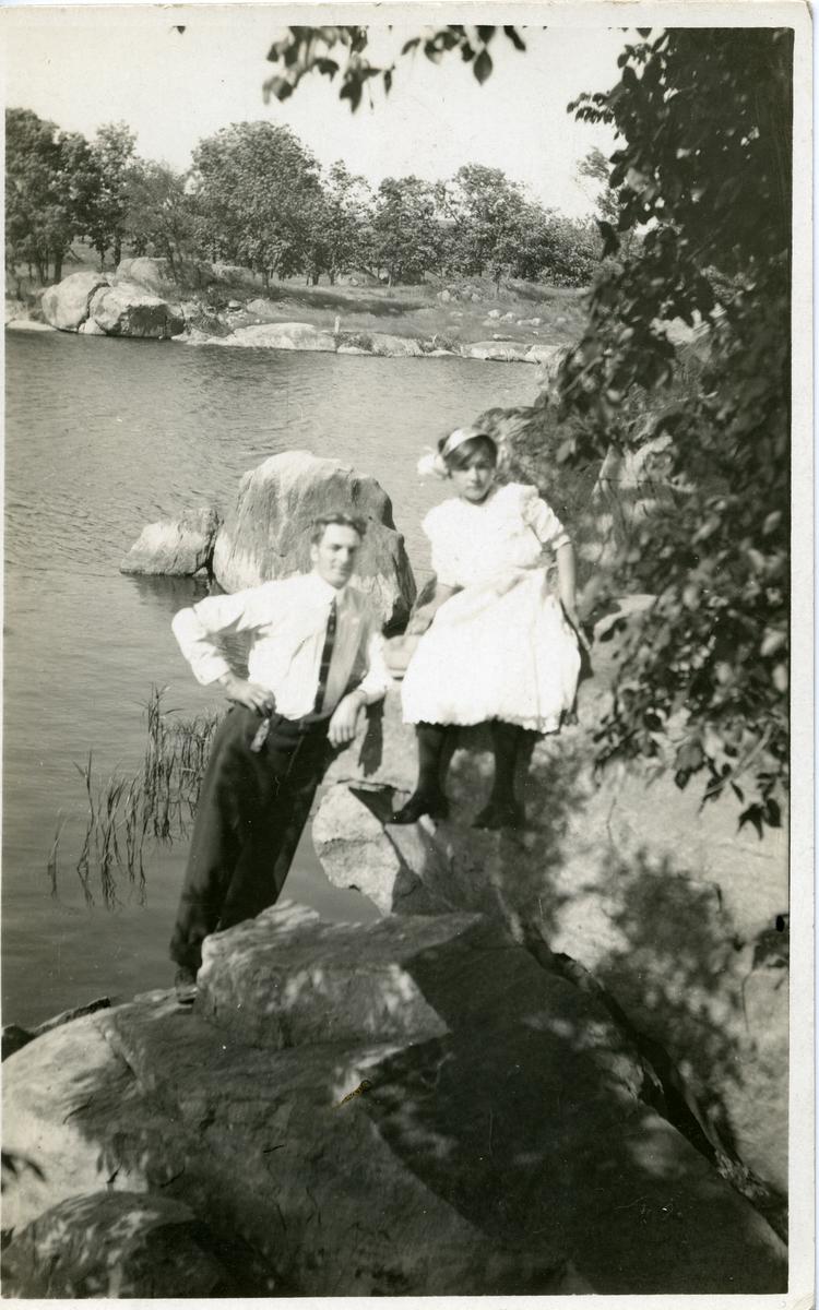 Kvinne og mann avbildet ved vann. Kvinne er iført kjole og mannen med skjorte og slips. Postkort.