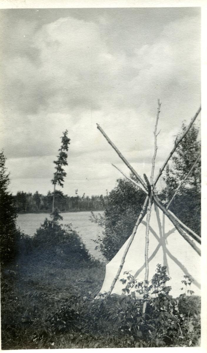 BIldet viser et telt og en uferdig tipi ved bredden av et vann eller en elv.