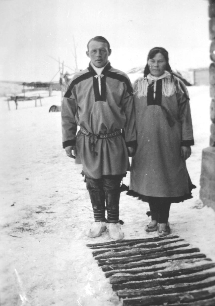 En mann, og ei kvinne kledt i samekofter, poserer ute foran et tun. På bena har de skaller. Bildet er muligens tatt innover Varangerfjorden, eller i Tana