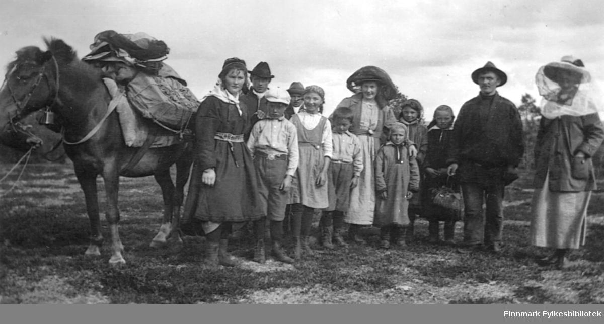På tur til å gå over fjellet fra Karasjok til Tverrelvdalen i Alta. På bildet står Karen Thomine Lovise Johansen kledt i en samedrakt med belte og kniv, ved siden av kløvhesten klar til å dra. Hesten er lastet på ryggen. Den har seletøy på seg og en bjelle under halsen. Ellers på bildet er førere og folk som fulgte med et lite stykke. Navn på noen av barn er Georg, Alfhild, Oskar (etternavn Næss?). Kvinnen i midten er Marie (Maja) Kristensen, som var gift med Karen Thomine Lovise sin bror Nils Kristensen (og senere med Jens Johnsen i Hammerfest). På turen over fjellet overnattet de fire netter. Fra Karasjok ble det Ravnestua, Mollesjokk, Stippanatsje og Jotka. Turene måtte gjøre om sommeren. Flere av barna er kledt i samedrakter. De to andre kvinnene på bildet har myggnett på hodet.  Bildet er tatt av Anna Næss, og de tre navngitte barna er hennes. Karen Thomine, Marie og Anna (fotografen) var søstre.