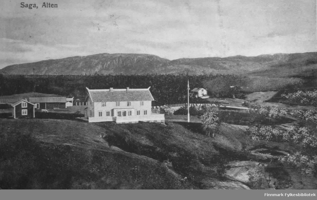 Oversiktsbilde fra villaen Saga i Alta. Dette er muligens et postkort. Teksten på bildet er Saga, Alten. I midten av bildet ligger villaen som er bygget i drakestil. Til venstre for det ligger det flere små hus. En hest står på tunet. Det store huset har veranda på flere sider. Taket har utskjæringer. Det står en flaggstang ved siden av huset. Et annet hus ligger til høyre i bildet. Det er skog og fjell i bakgrunnen