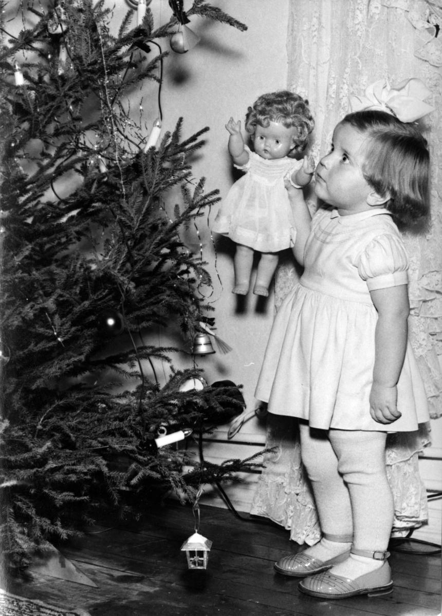 Foto av ei lita jente som viser fram juetreet til dokka si.