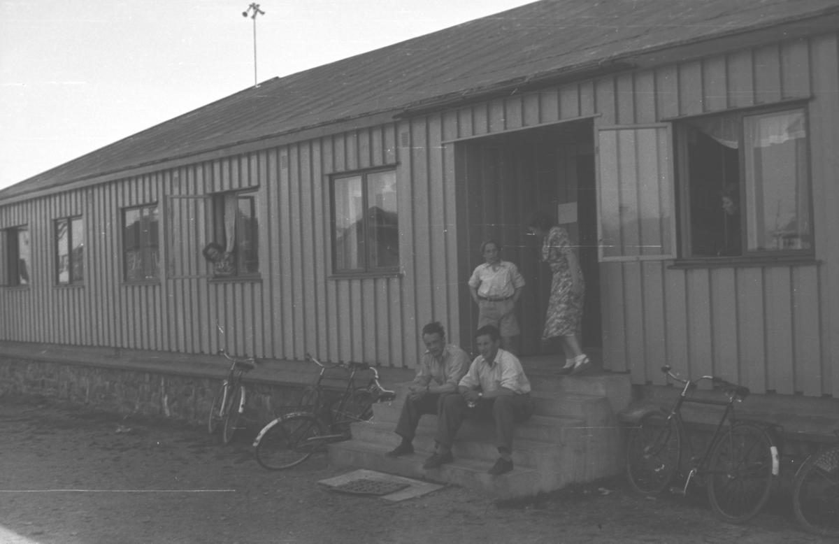 Fylkesmannens brakke i Vadsø like etter krigen. Noen mennesker, muligens ansatte, er på trappa og i vinduer og flere sykler står utenfor. Personene er ukjent.