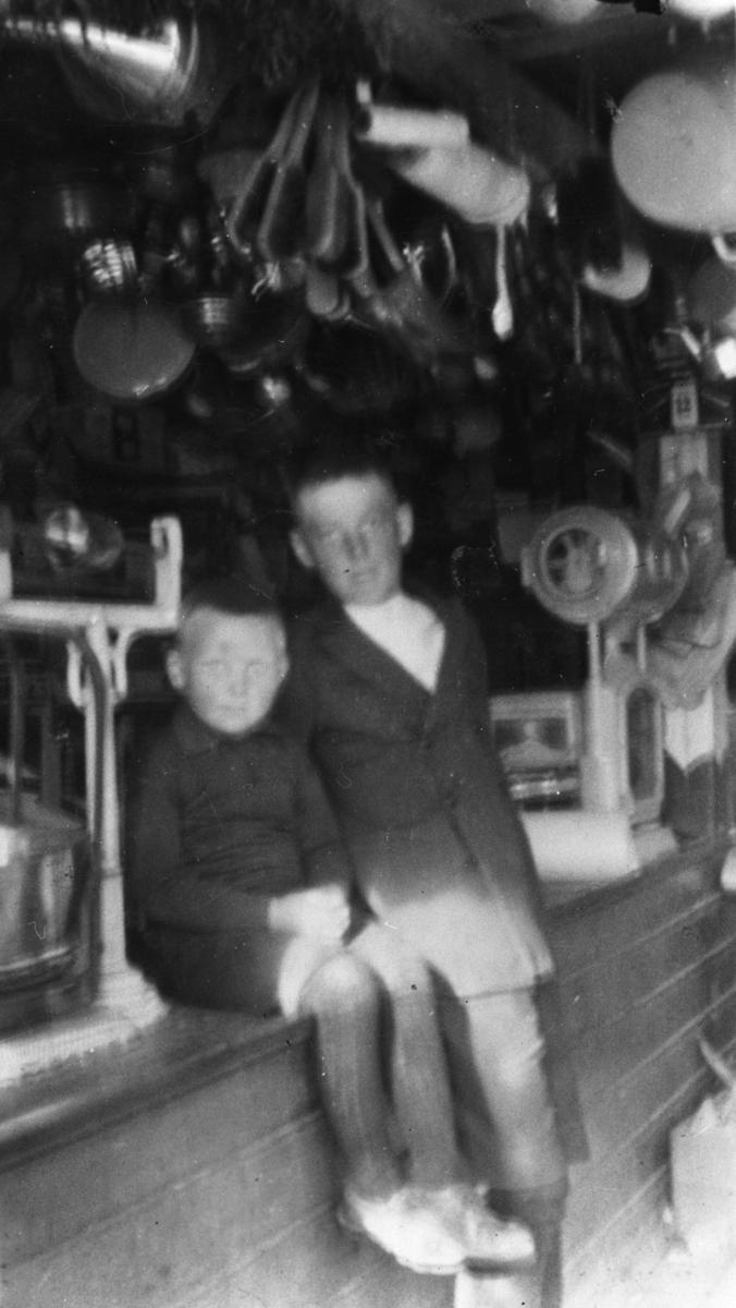 Bildet er tatt fra forretningen til Gaare, ca 1916-17. Fra venstre Bjarne Jørstad og Arnold Rolfsen. Forretningen var i kjelleren til Odin Kvello. Guttene sitter på disken ved siden av en vekt. I taket henger det forskjellig utstyr.