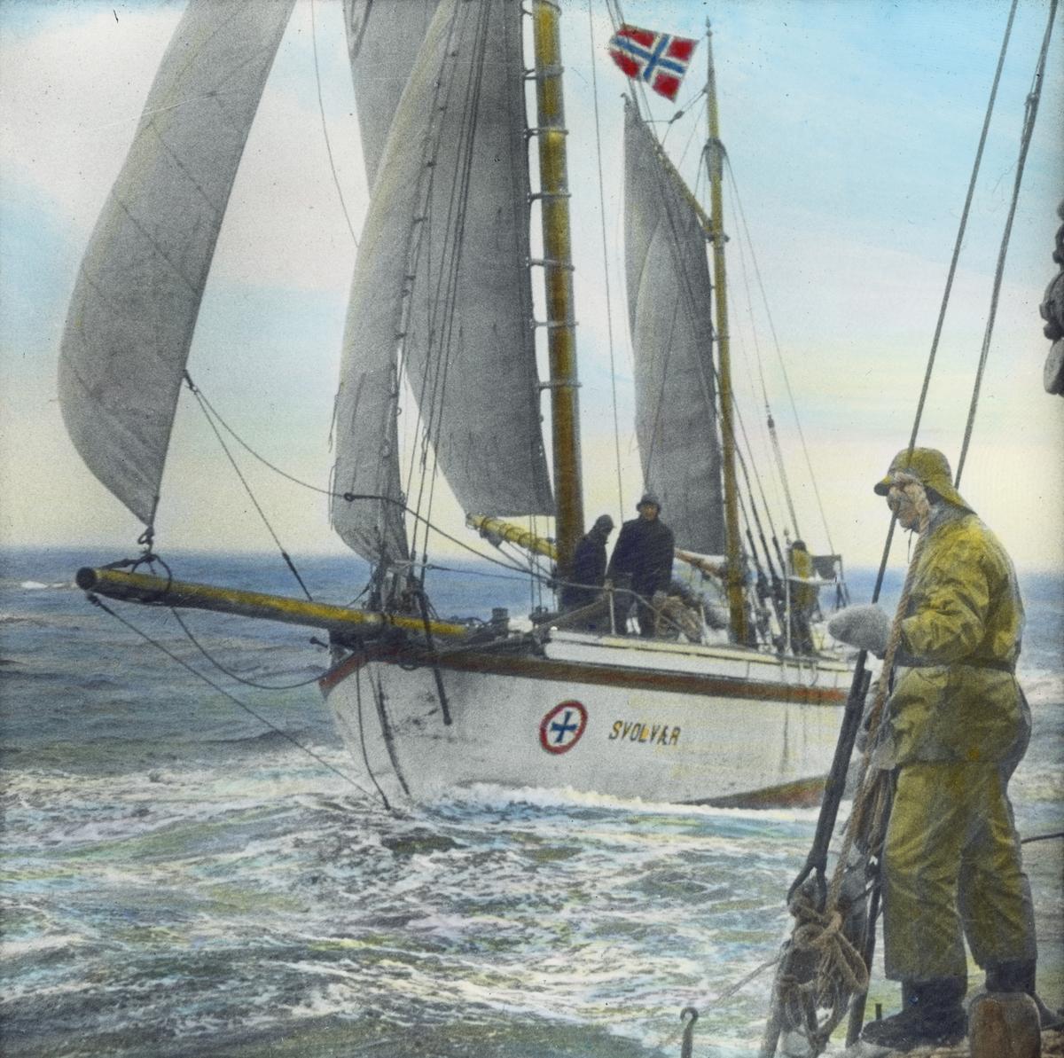 """Håndkolorert dias. Redningsskøyta """"Svolvær"""" seiler. I forgrunnen står en mann kledd i oljehyre og sydvest ombord i en annen båt."""