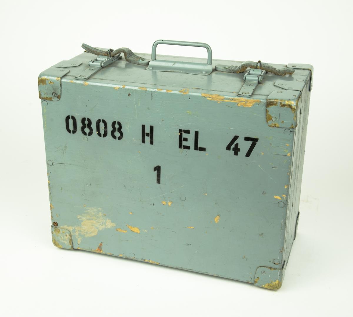 """Sektorfyr EL 47 NIFE. Sektorfyren har som en stickpropp i botten. Uppe på fyren finns ett vattenpass. Fyren förvaras i en trälåda, på trälådan står """"0808 H EL 47 1""""."""