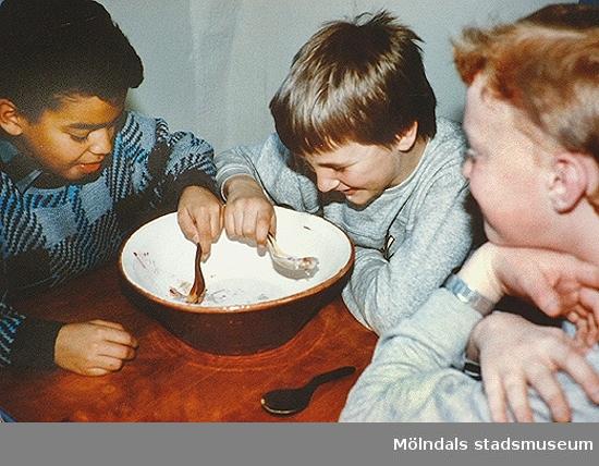Barn som äter korngröt ur en gemensam skål. Pedagogik på Mölndals museum, okänt årtal.