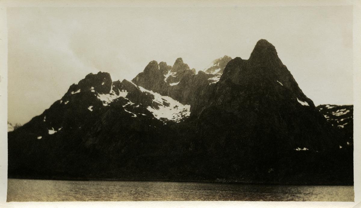 Ukjente snødekte fjell. Fotografert fra båt. Bildet er muligens tatt i Nordland.