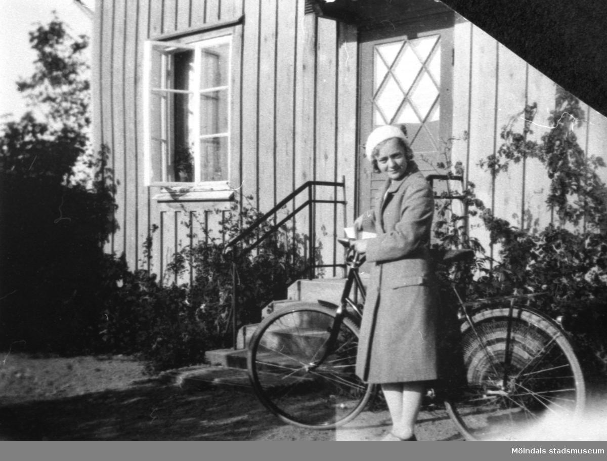 Rosa Pettersson f. Krantz vid sin nya cykel, troligtvis 1932. Hon står utanför personalbostaden på Stretered.