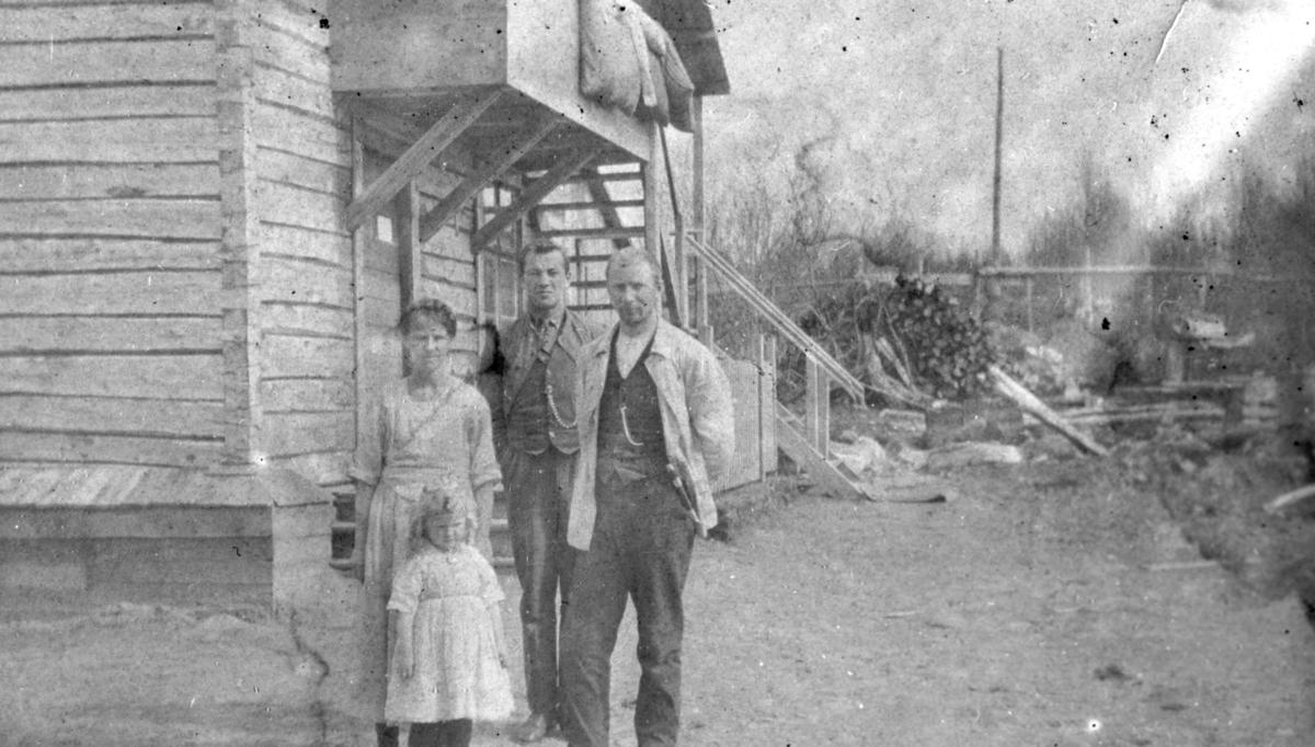 På bildet ser vi tre kvinner utenfor et hus i Langfjordbotn.