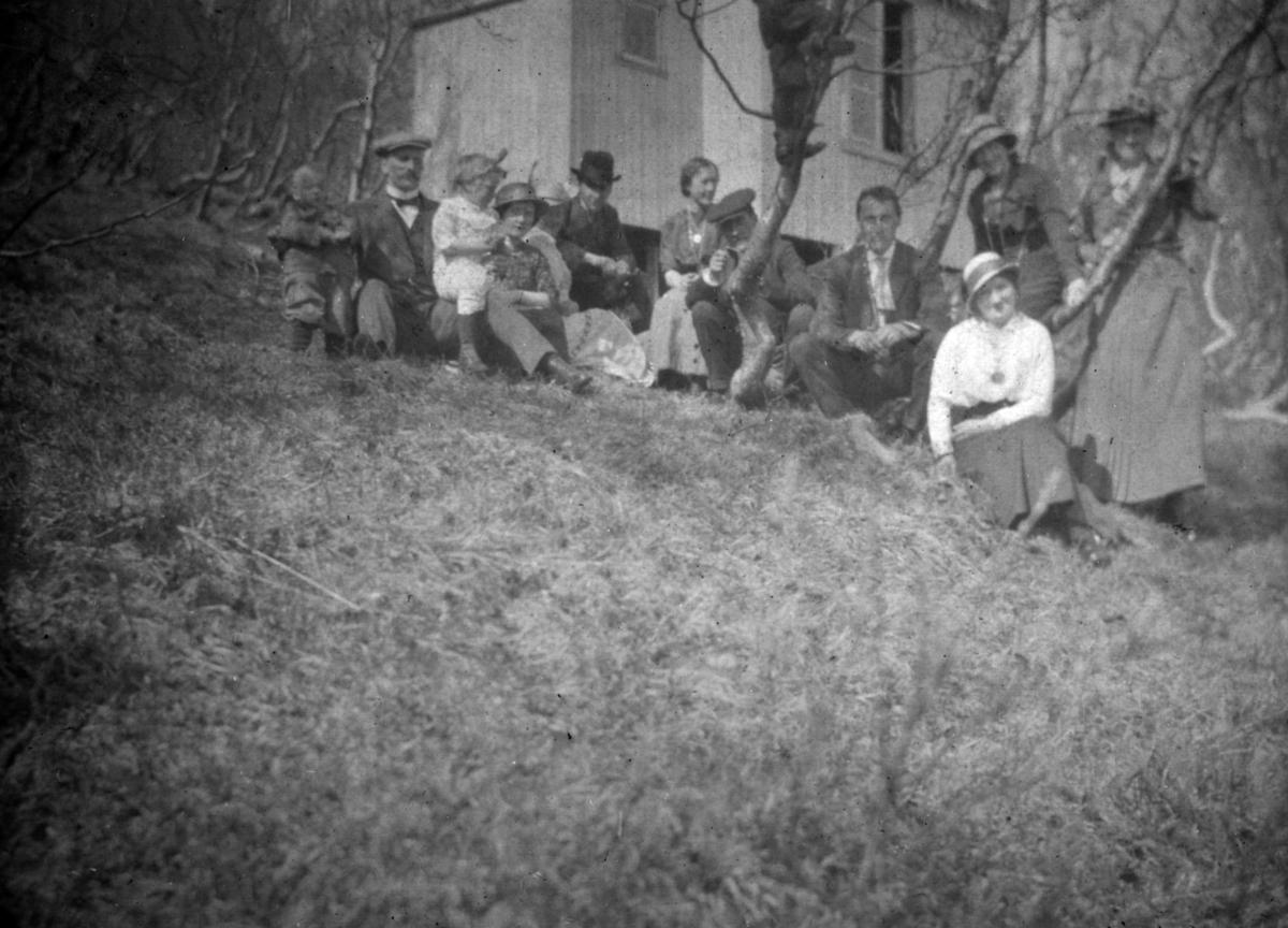 """En gruppe menn, kvinner og barn har slengt seg ned på gresset ved lysthuset i """"Loppen"""". Bilde tatt 30. juni 1918 (?)."""