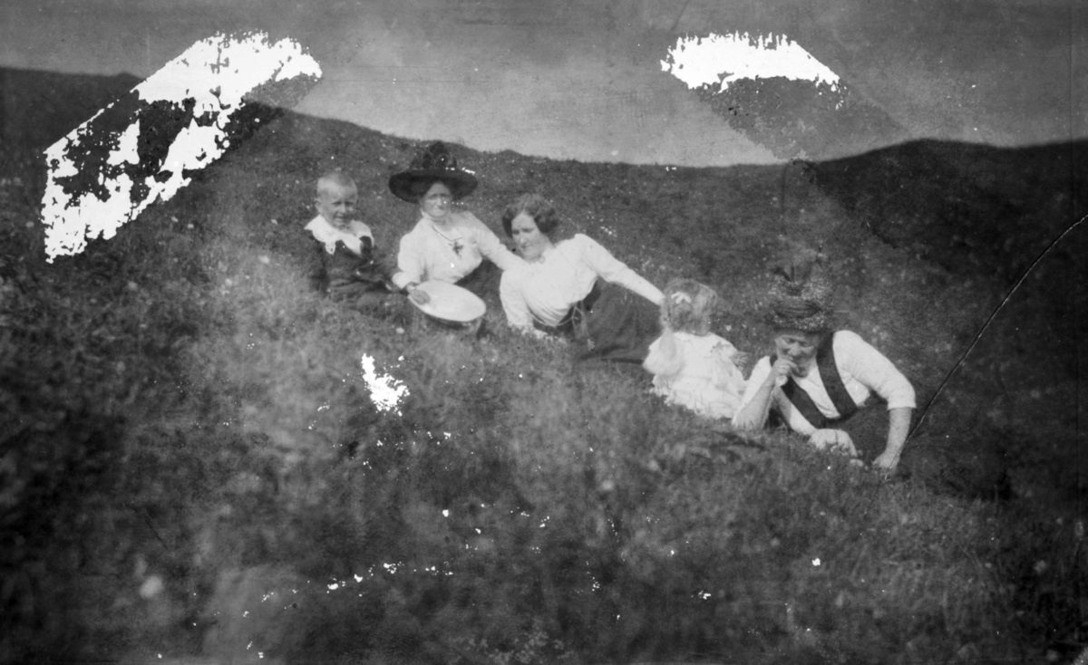 """""""På Kønes. Loppen."""" Tre kvinner, en liten gutt og jente ligger i skråningen. Kvinnene er kledd i kjole og hatt. Kvinnen t.v. har pyntet seg med smykke. Gutten har på seg en dekorativ drakt. Jenta har sløyfe i håret."""
