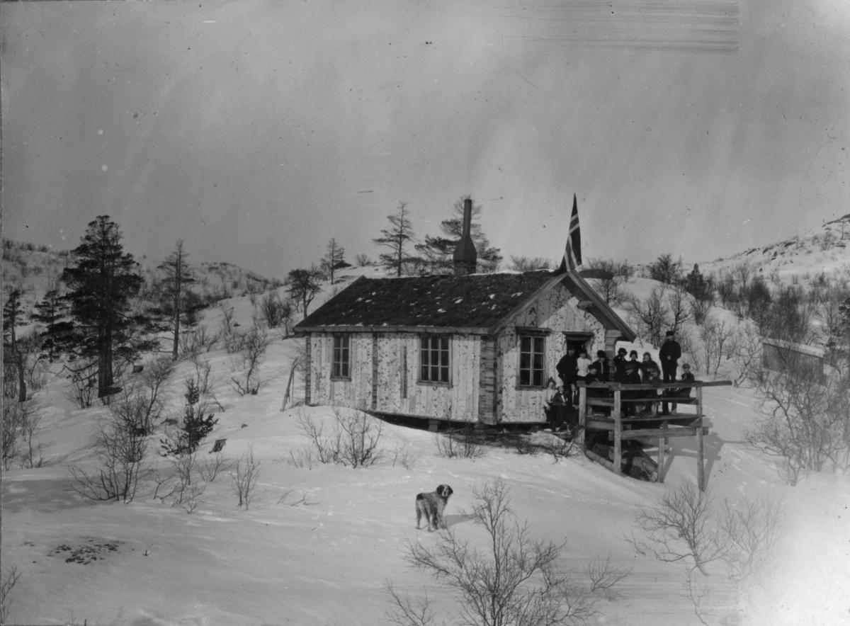Hytte kledd i never, muligens ved Ørnevatnet. En del folk står på trammen og flagget er heist.På midten av bilde kan man se en hund.