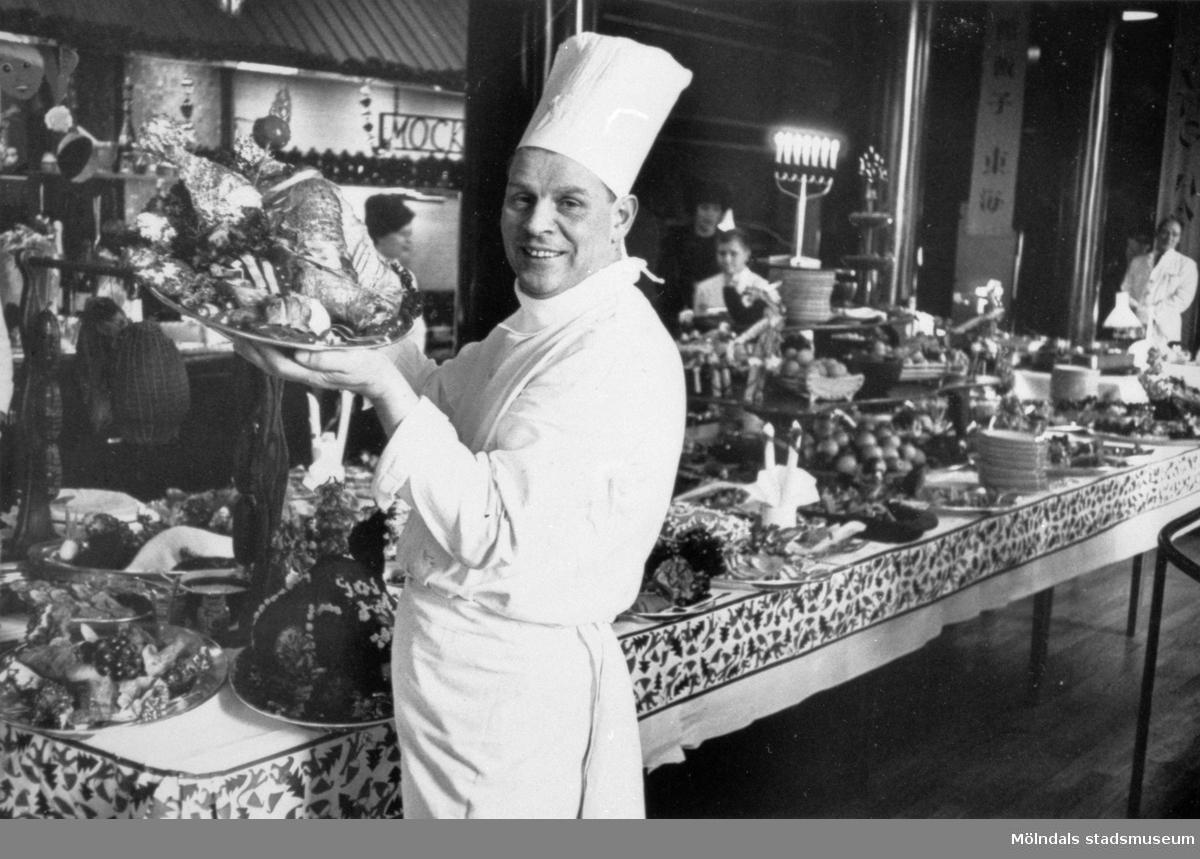 Gunnebo slotts egen kock Ruben Bohm (anställd 1938-1943). Han står med ett fat i handen bredvid ett långbord fyllt med mat. I bakgrunden ses serveringspersonal, 1940-tal.