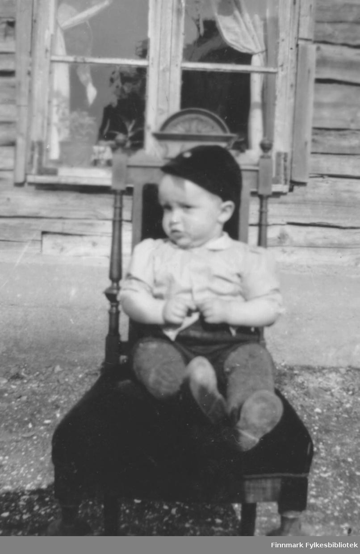 En ung Håkon Bauna sitter i sommersola utenfor et hus i Skallelv.