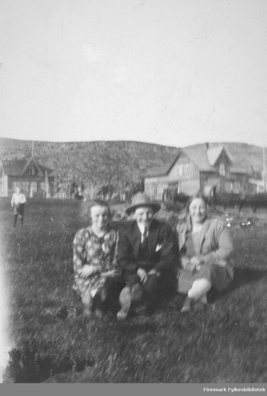 Tre personer sitter i gresset en sommerdag i Hamningberg. Noen av de er fra venstre: Aline Strige, antatt Aksel Johannesen i midten og Gudrun Bauna til høyre. Fotografert av Håkon Bauna.