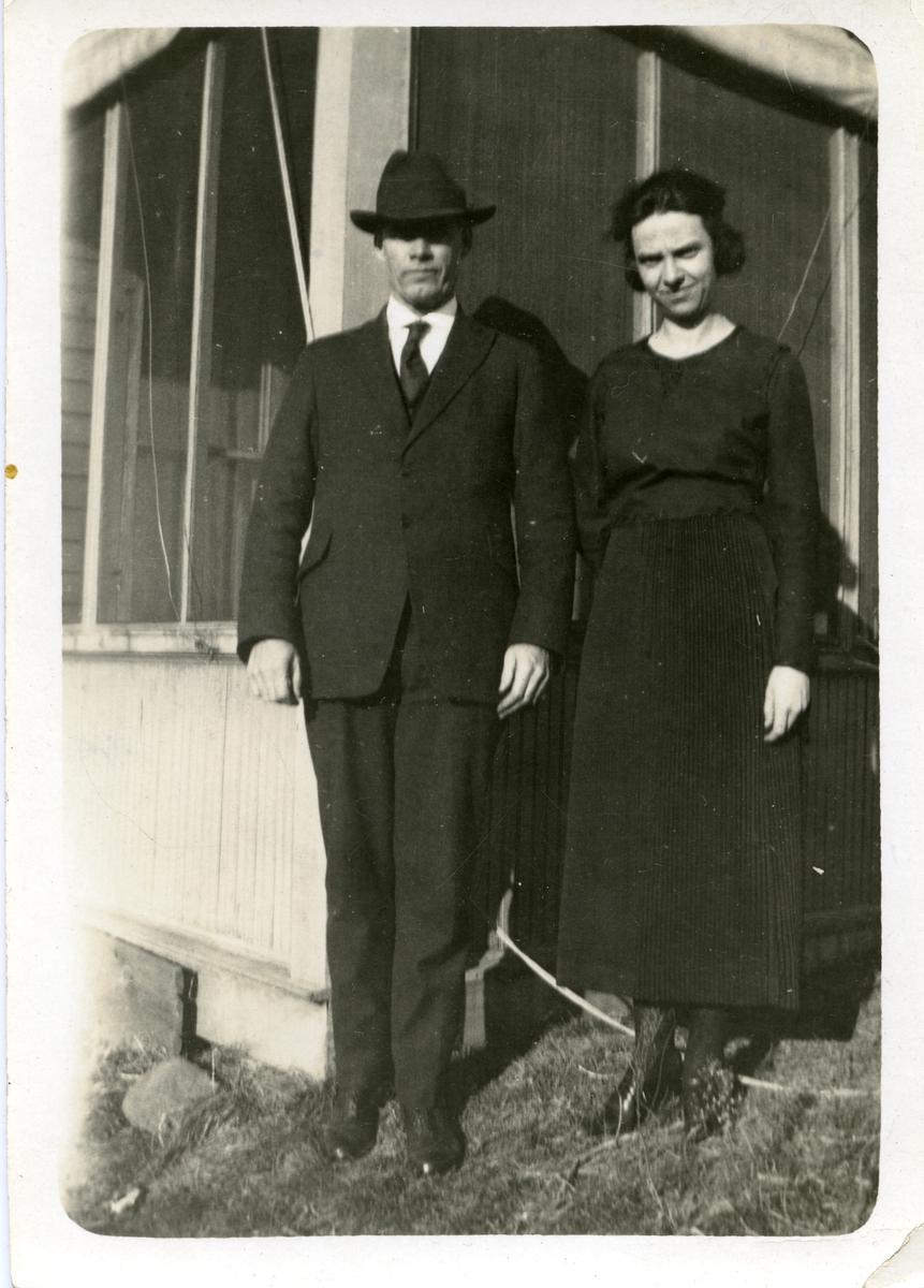 Ungt par oppstilt utenfor et hus. Hun i mørk kjole, og han i mørk dress, slips og hatt.