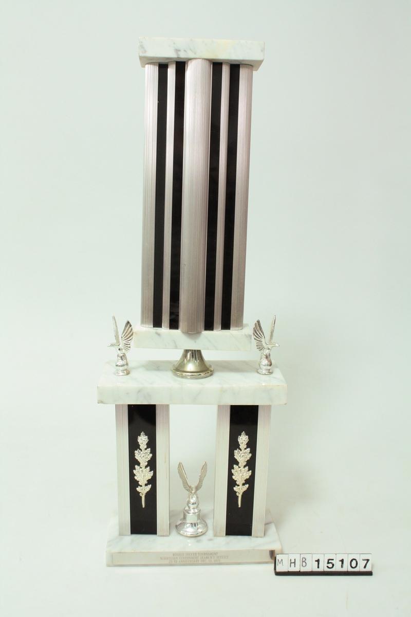 Premie formet som en sokkel i to etasjer med mamorflater og metallsøyler. Tre ørne-figurer.
