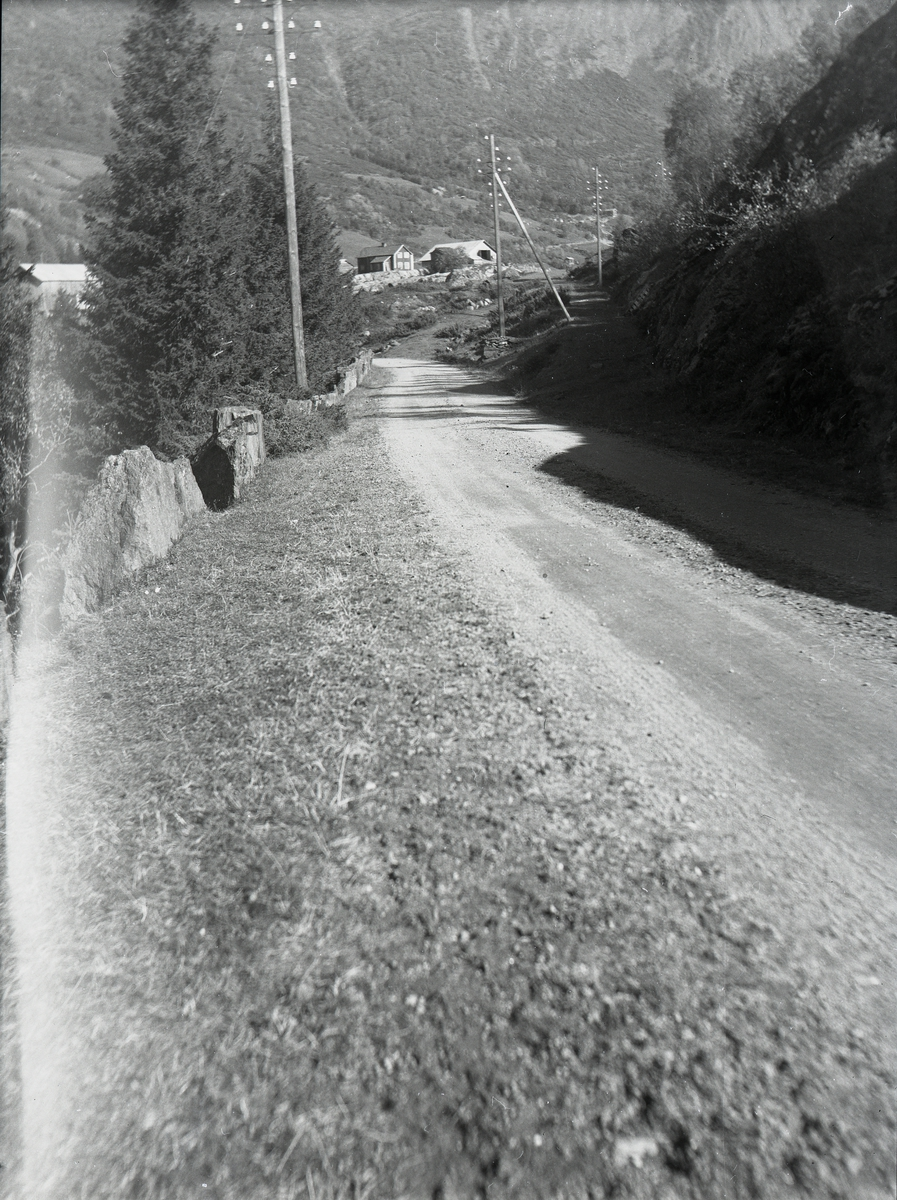 Avbildet en grusvei opp mot et hus.