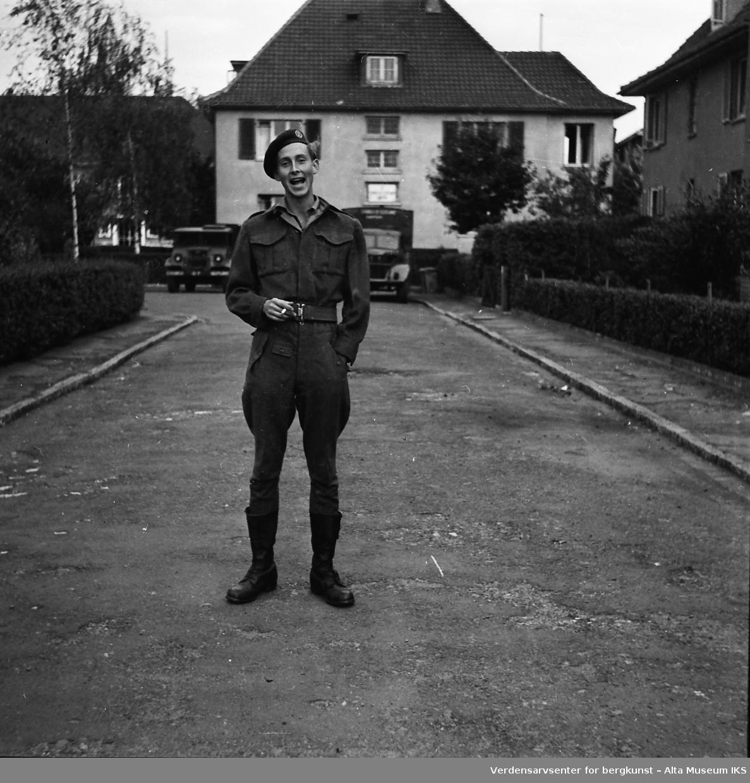 En ung norsk soldat står på en gate med en sigarett i hånden. I bakgrunnen står det flere militære kjøretøy.