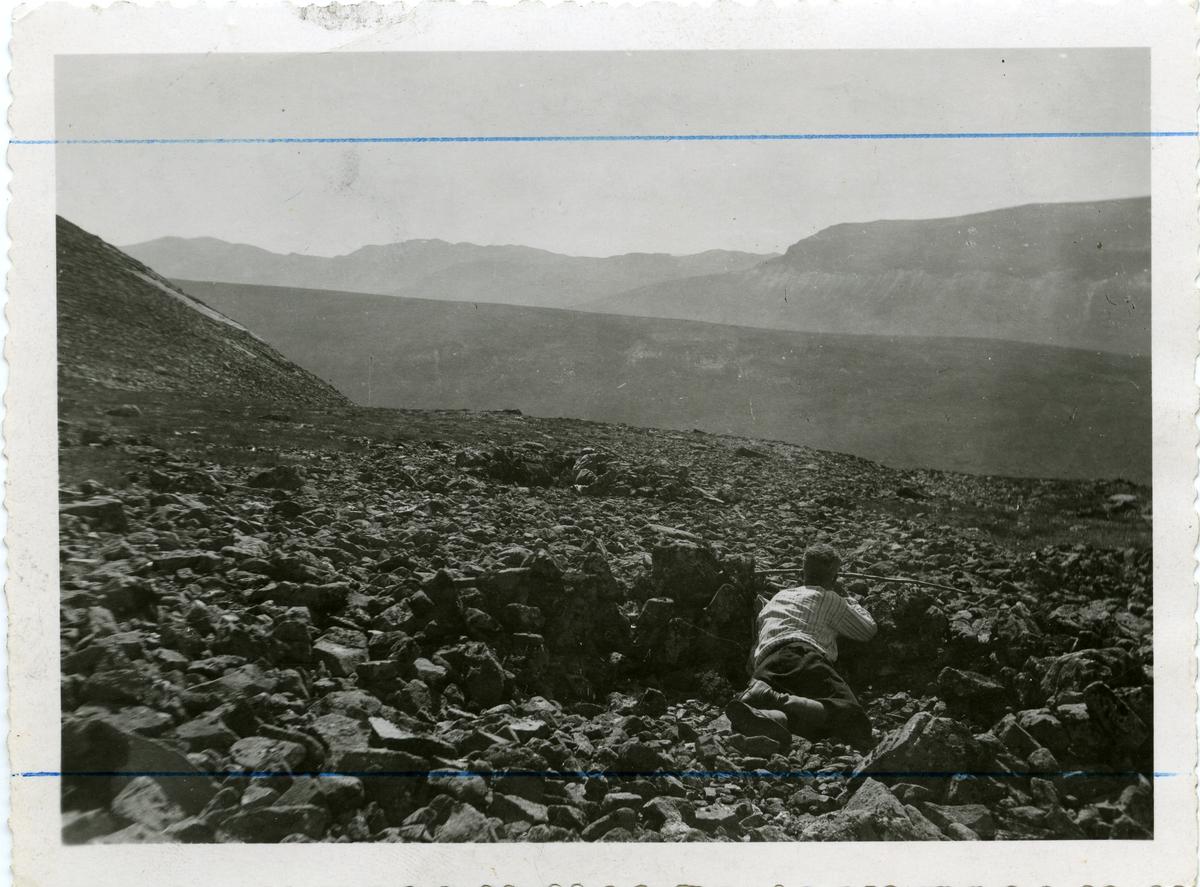 """Mann liggende bak en """"Steinmur"""", i et """"bøgahi."""" Bildet er fra Vang i Valdres."""