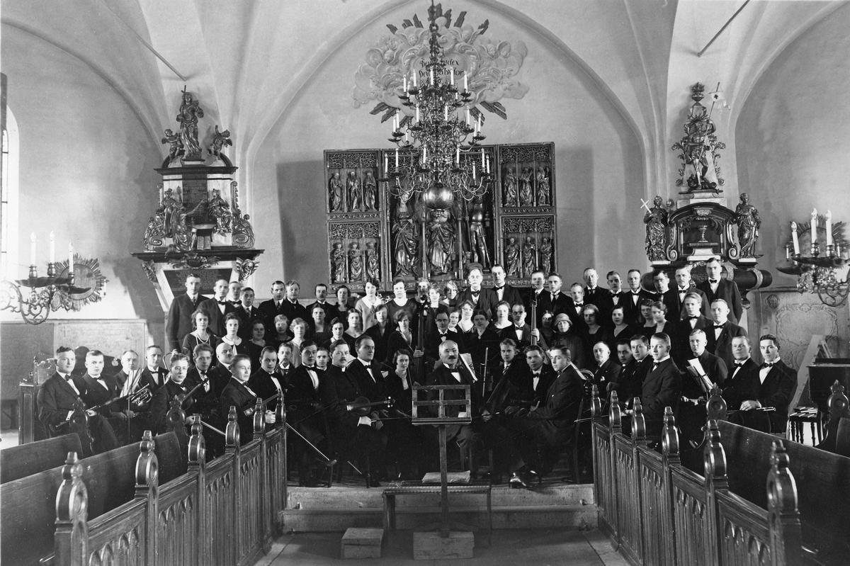 Konsert i Köpings kyrka. Margareta Axelssons farfar Bror finns med på bild. Han spelar, och sitter bakom mannen med rundkragen.